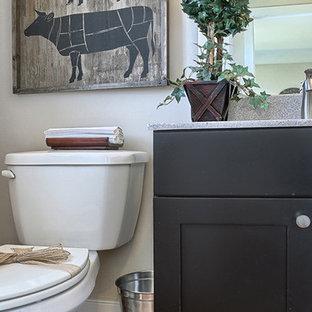На фото: туалет среднего размера в стиле кантри с черными фасадами, паркетным полом среднего тона, фасадами в стиле шейкер, раздельным унитазом, бежевыми стенами и столешницей терраццо с