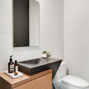 Aménagement d'un WC et toilettes contemporain de taille moyenne avec un placard à porte plane, des portes de placard en bois clair, un WC à poser, un mur blanc et un plan de toilette en bois.