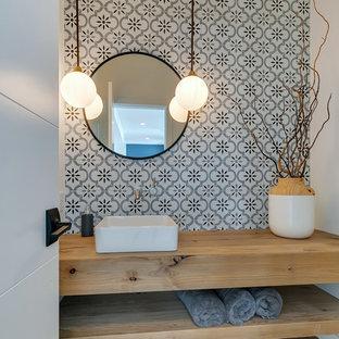 Lantlig inredning av ett litet brun brunt toalett, med öppna hyllor, skåp i mellenmörkt trä, en toalettstol med separat cisternkåpa, grå kakel, keramikplattor, grå väggar, mellanmörkt trägolv, ett fristående handfat, träbänkskiva och brunt golv