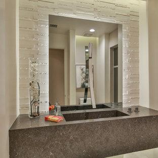 Неиссякаемый источник вдохновения для домашнего уюта: туалет среднего размера в современном стиле с унитазом-моноблоком, белой плиткой, плиткой из известняка, бежевыми стенами, полом из керамогранита, монолитной раковиной, столешницей из известняка, бежевым полом и серой столешницей