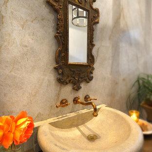На фото: большой туалет в средиземноморском стиле с фасадами островного типа, фасадами цвета дерева среднего тона, серой плиткой, белой плиткой, настольной раковиной, мраморной плиткой и коричневой столешницей с