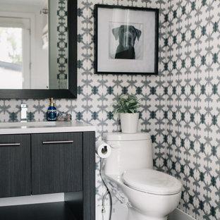 Immagine di un bagno di servizio chic con ante lisce, ante nere, pareti multicolore, lavabo sottopiano, pavimento nero e top bianco