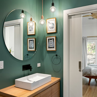 Photo of a contemporary powder room in Melbourne with flat-panel cabinets, medium wood cabinets, green walls, a vessel sink, wood benchtops, grey floor, brown benchtops and a floating vanity.