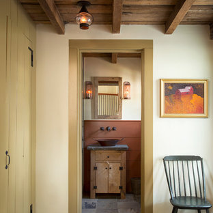 Imagen de aseo campestre, pequeño, con lavabo sobreencimera, puertas de armario con efecto envejecido, encimera de esteatita, baldosas y/o azulejos grises, paredes blancas, suelo de pizarra, armarios tipo mueble y encimeras grises