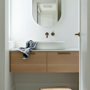 This is an example of a small contemporary powder room in Perth with medium wood cabinets, white walls, cement tiles, engineered quartz benchtops, beige floor, a floating vanity, flat-panel cabinets, a vessel sink and white benchtops.