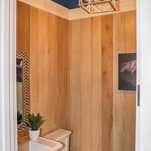 Cette photo montre un petit WC et toilettes chic avec un WC à poser, un mur marron, un sol en bois brun et un lavabo de ferme.