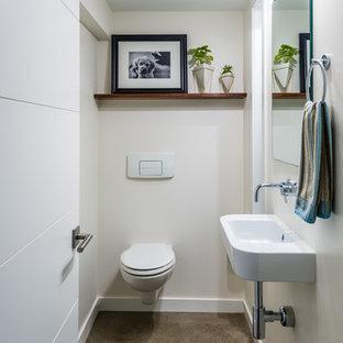 Idées déco pour un petit WC et toilettes contemporain avec un WC suspendu, béton au sol, un lavabo suspendu, un mur beige et un sol gris.