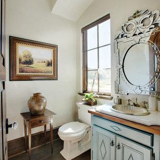 Cette photo montre un petit WC et toilettes chic avec un placard avec porte à panneau encastré, des portes de placard turquoises, un WC séparé, un carrelage beige, un mur beige, un sol en bois foncé, un lavabo posé, un plan de toilette en quartz, un sol marron et un plan de toilette blanc.