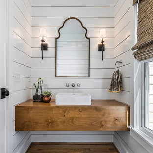 This is an example of a small country powder room in Other with white walls, medium hardwood floors, a vessel sink, wood benchtops, brown benchtops, brown floor, flat-panel cabinets and medium wood cabinets.