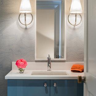 Ejemplo de aseo contemporáneo, de tamaño medio, con lavabo bajoencimera, armarios con paneles lisos, puertas de armario azules, encimera de cuarzo compacto y encimeras blancas
