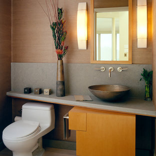 Small trendy travertine floor powder room photo in San Francisco with a vessel sink, flat-panel cabinets, a one-piece toilet, beige walls and medium tone wood cabinets