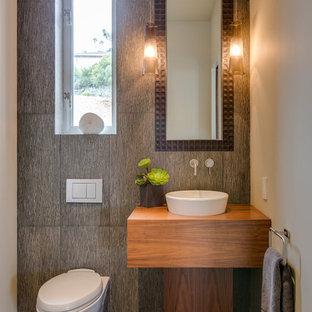 Modelo de aseo contemporáneo con lavabo sobreencimera, puertas de armario de madera oscura, sanitario de pared, baldosas y/o azulejos grises, paredes beige y suelo de cemento