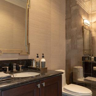 サンフランシスコの中くらいのトランジショナルスタイルのおしゃれなトイレ・洗面所 (レイズドパネル扉のキャビネット、茶色いキャビネット、一体型トイレ、グレーのタイル、ミラータイル、グレーの壁、磁器タイルの床、コンソール型シンク、大理石の洗面台、グレーの床、黒い洗面カウンター) の写真