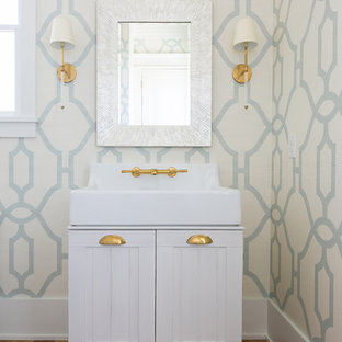 Photo of a mid-sized country powder room in Charleston with furniture-like cabinets, white cabinets, brown floor, blue walls, medium hardwood floors, an integrated sink, engineered quartz benchtops and white benchtops.