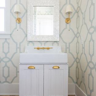 На фото: туалет среднего размера в стиле кантри с фасадами островного типа, белыми фасадами, коричневым полом, синими стенами, паркетным полом среднего тона, монолитной раковиной, столешницей из искусственного кварца и белой столешницей с