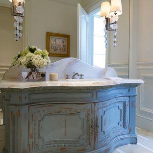 Cette image montre un très grand WC et toilettes traditionnel avec un placard en trompe-l'oeil, des portes de placard en bois vieilli, un lavabo encastré, un plan de toilette en onyx et des dalles de pierre.