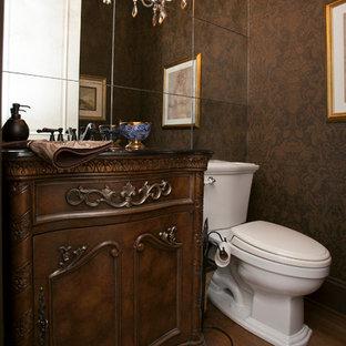 На фото: огромный туалет в викторианском стиле с врезной раковиной, темными деревянными фасадами, столешницей из гранита, раздельным унитазом, коричневыми стенами и паркетным полом среднего тона