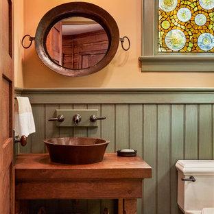 Cette photo montre un WC et toilettes montagne avec un placard en trompe-l'oeil, des portes de placard en bois brun, un mur orange, une vasque, un plan de toilette en bois, un sol gris et un plan de toilette marron.