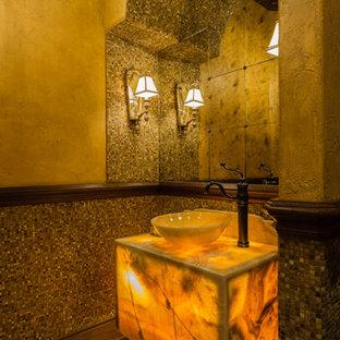 На фото: туалет в средиземноморском стиле с разноцветной плиткой, керамической плиткой, бежевыми стенами, полом из терракотовой плитки, настольной раковиной, столешницей из оникса и коричневым полом с