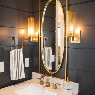 Cette image montre un petit WC et toilettes traditionnel avec un placard à porte shaker, des portes de placard en bois brun, un mur noir, un lavabo encastré, un plan de toilette beige, meuble-lavabo encastré et du lambris de bois.