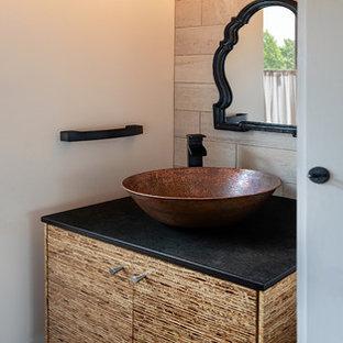 フィラデルフィアのラスティックスタイルのおしゃれなトイレ・洗面所 (フラットパネル扉のキャビネット、中間色木目調キャビネット、ベージュのタイル、石タイル、ベージュの壁、濃色無垢フローリング、ベッセル式洗面器、黒い洗面カウンター) の写真