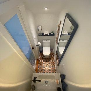 Exemple d'un petit WC et toilettes moderne avec un placard à porte plane, des portes de placard blanches, un WC à poser, un carrelage blanc, des carreaux de céramique, un mur blanc, un sol en carrelage de céramique, un lavabo suspendu, un sol multicolore, un plan de toilette blanc, meuble-lavabo suspendu et un plafond voûté.