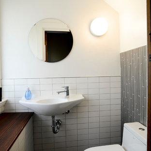 Стильный дизайн: маленький туалет в стиле модернизм с открытыми фасадами, раздельным унитазом, белой плиткой, керамической плиткой, белыми стенами, полом из керамической плитки, подвесной раковиной и серым полом - последний тренд