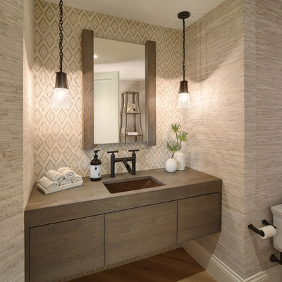 Example of a beach style light wood floor powder room design in Cleveland with flat-panel cabinets, beige walls and an undermount sink