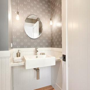 На фото: с высоким бюджетом туалеты в стиле кантри с столешницей из гранита, паркетным полом среднего тона, серыми стенами и подвесной раковиной