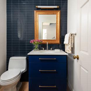 Пример оригинального дизайна: маленький туалет в современном стиле с плоскими фасадами, синими фасадами, унитазом-моноблоком, синей плиткой, керамической плиткой, белыми стенами, светлым паркетным полом, врезной раковиной, столешницей из искусственного кварца, белой столешницей и бежевым полом