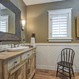 На фото: туалеты в классическом стиле с синими фасадами, коричневыми стенами, темным паркетным полом, накладной раковиной, столешницей из дерева, коричневым полом и коричневой столешницей
