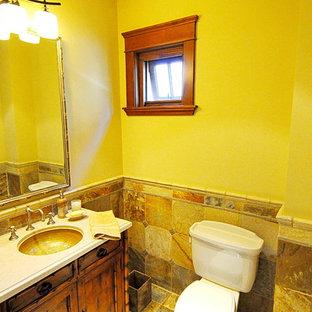 Cette image montre un WC et toilettes ethnique de taille moyenne avec un placard en trompe-l'oeil, des portes de placard en bois vieilli, un WC séparé, un carrelage jaune, un carrelage de pierre, un mur jaune, un sol en bois clair, un lavabo encastré, un plan de toilette en travertin et un sol multicolore.