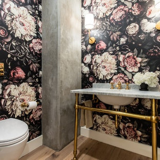 Inspiration for a transitional medium tone wood floor and beige floor powder room remodel in Dallas with a wall-mount toilet, multicolored walls, a console sink, marble countertops and gray countertops