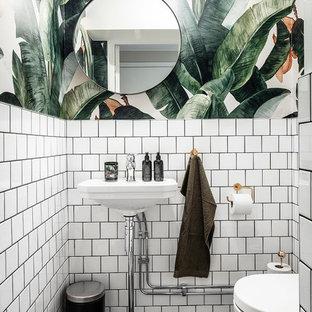 Inredning av ett minimalistiskt litet svart svart toalett, med öppna hyllor, vita skåp, en vägghängd toalettstol, vit kakel, keramikplattor, vita väggar, klinkergolv i keramik, svart golv och ett piedestal handfat