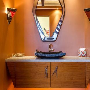 Foto de aseo de estilo zen, de tamaño medio, con puertas de armario de madera oscura, parades naranjas, lavabo sobreencimera, encimera de granito y encimeras grises