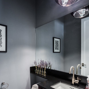 Photo of a small contemporary cloakroom in New York with freestanding cabinets, dark wood cabinets, a one-piece toilet, grey walls, slate flooring, a submerged sink, granite worktops and black worktops.