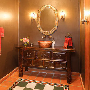 This is an example of a medium sized mediterranean cloakroom in San Diego with freestanding cabinets, dark wood cabinets, orange tiles, multi-coloured tiles, terracotta flooring, a vessel sink and wooden worktops.