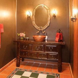 Foto di un bagno di servizio mediterraneo di medie dimensioni con consolle stile comò, ante in legno bruno, piastrelle arancioni, piastrelle multicolore, pavimento in terracotta, lavabo a bacinella e top in legno
