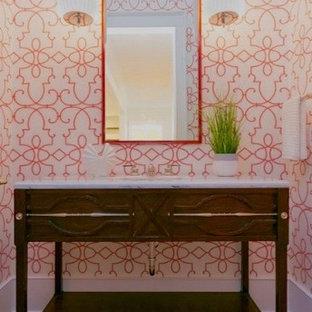 Foto di un bagno di servizio tradizionale di medie dimensioni con consolle stile comò, ante marroni, pareti arancioni, pavimento in legno massello medio, lavabo da incasso, top in marmo e pavimento marrone