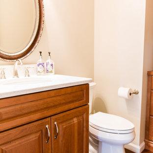 Свежая идея для дизайна: туалет среднего размера в классическом стиле с фасадами с выступающей филенкой, фасадами цвета дерева среднего тона, раздельным унитазом, бежевыми стенами, полом из бамбука, врезной раковиной, столешницей из искусственного кварца и коричневым полом - отличное фото интерьера