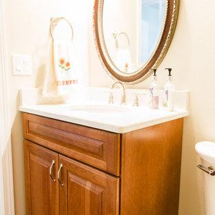 Пример оригинального дизайна: туалет среднего размера в классическом стиле с фасадами с выступающей филенкой, фасадами цвета дерева среднего тона, раздельным унитазом, бежевыми стенами, полом из бамбука, врезной раковиной, столешницей из искусственного кварца и коричневым полом