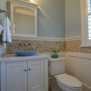 Photo of a classic cloakroom in New York with a vessel sink, shaker cabinets, white cabinets, engineered stone worktops, a two-piece toilet, multi-coloured tiles, pebble tiles, blue walls and porcelain flooring.