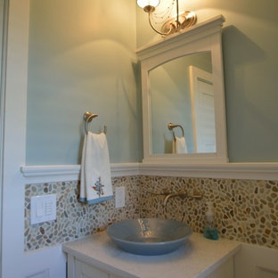 Photo of a traditional cloakroom in New York with a vessel sink, shaker cabinets, white cabinets, engineered stone worktops, a two-piece toilet, multi-coloured tiles, pebble tiles, blue walls and porcelain flooring.
