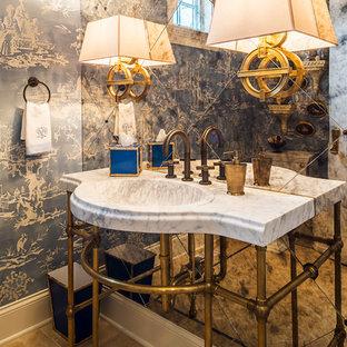 シカゴの中くらいのエクレクティックスタイルのおしゃれなトイレ・洗面所 (分離型トイレ、ベージュのタイル、青い壁、大理石の床、コンソール型シンク、大理石の洗面台、ミラータイル) の写真