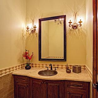 Неиссякаемый источник вдохновения для домашнего уюта: туалет среднего размера в классическом стиле с накладной раковиной, темными деревянными фасадами, мраморной столешницей, коричневой плиткой, каменной плиткой, бежевыми стенами, полом из травертина и фасадами островного типа
