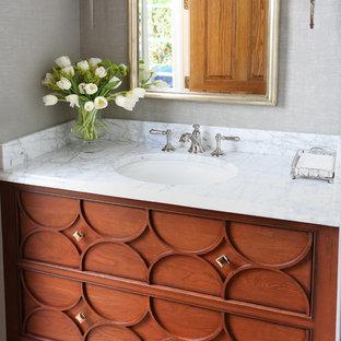 Стильный дизайн: маленький туалет в классическом стиле с фасадами островного типа, серыми стенами, светлым паркетным полом, мраморной столешницей и фасадами цвета дерева среднего тона - последний тренд