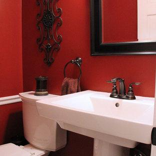 Пример оригинального дизайна интерьера: маленький туалет в классическом стиле с раковиной с пьедесталом, раздельным унитазом, красными стенами и полом из керамогранита