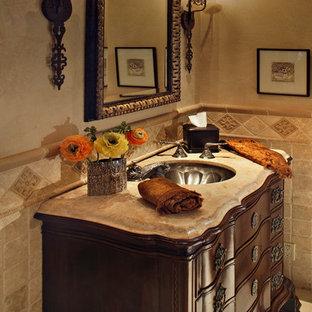 Réalisation d'un WC et toilettes tradition avec un placard en trompe-l'oeil, des portes de placard en bois sombre, du carrelage en travertin et un lavabo encastré.