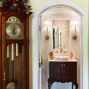 На фото: маленький туалет в классическом стиле с настольной раковиной, фасадами островного типа, темными деревянными фасадами, мраморной столешницей, белой плиткой, каменной плиткой, белыми стенами и мраморным полом с