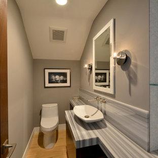 Idées déco pour un petit WC et toilettes contemporain avec un placard à porte plane, des portes de placard noires, un WC à poser, un mur gris, un sol en bois clair, une vasque et un plan de toilette en onyx.
